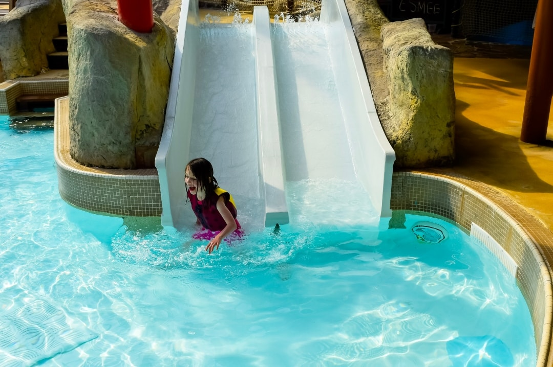 A photograph of a little girl going down a water slide ancing in the water at Splash Landings in Alton Towers - the little girl is wearing the Original Konfidence Swim Jacket and Konfidence Warma Wetsuit - Swimming With Konfidene At Splash Landings - Mrs H's favourite things