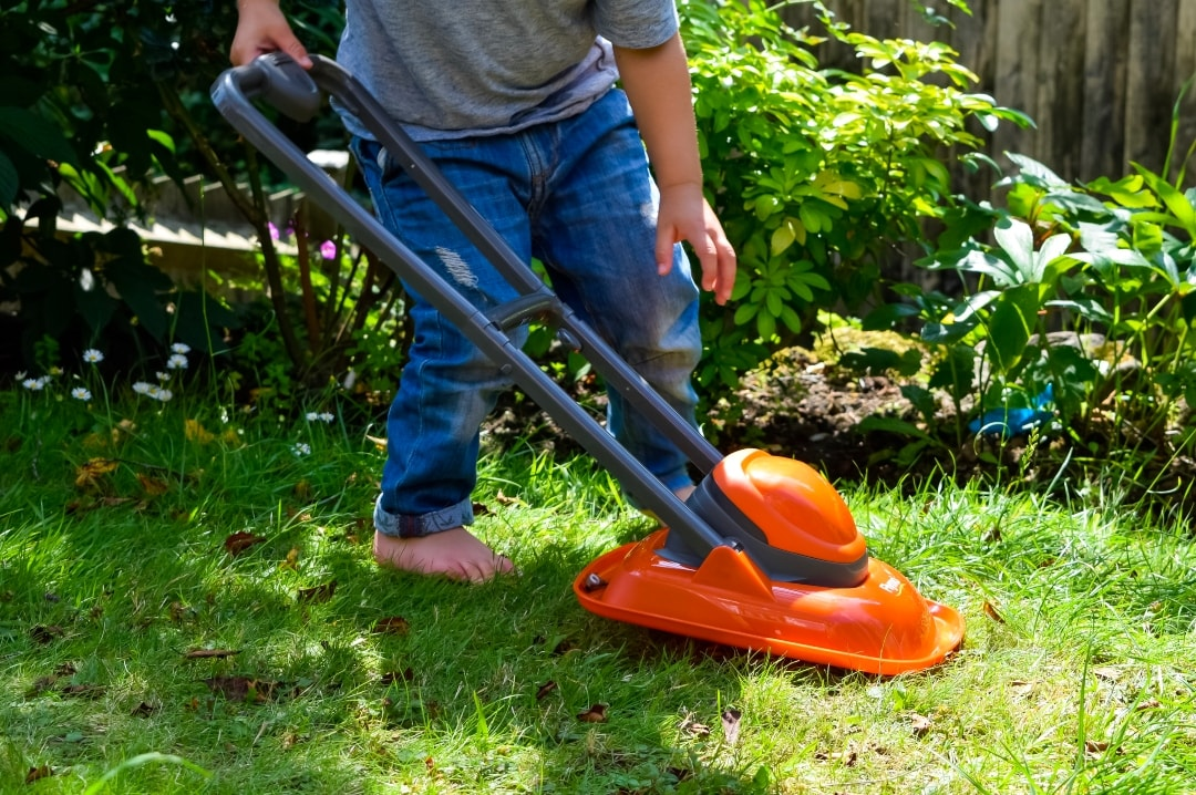 A photograph of a little boy playing with the Casdon Flymo Lawn Mower - Casdon Flymo Lawn Mower - A Review - Mrs H's favourite things
