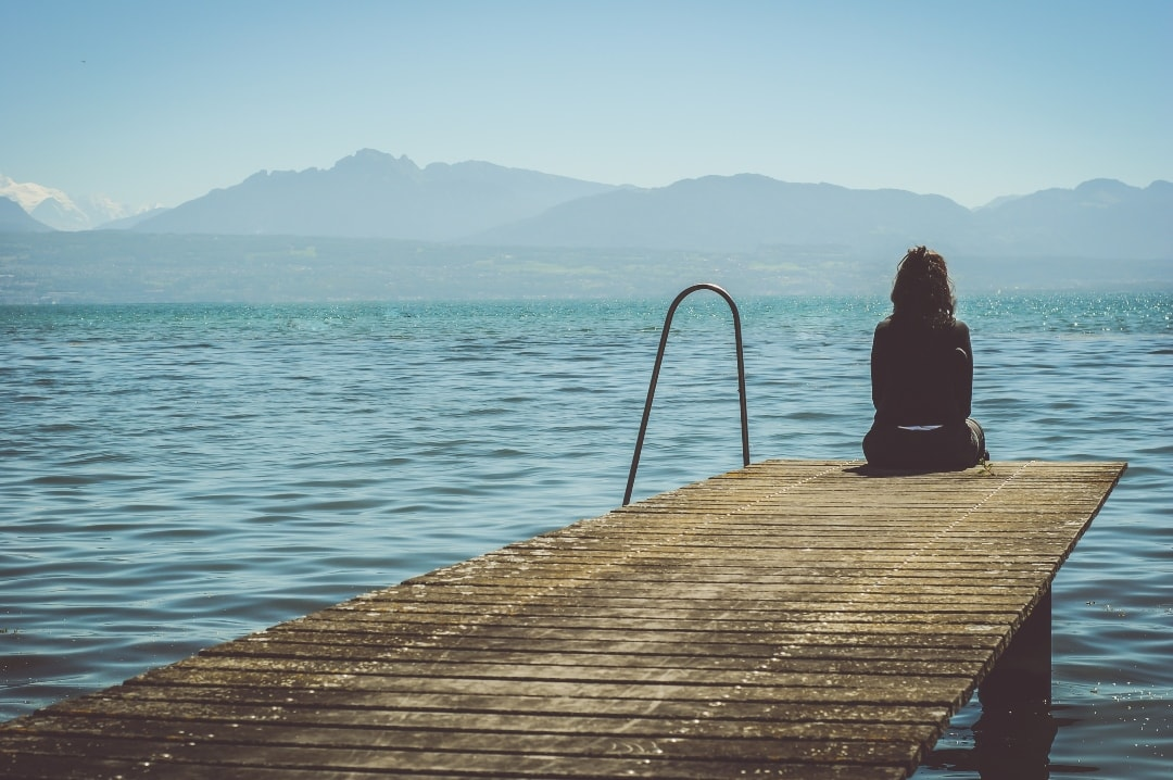 A photograph of a girl with her back to the camera and sitting on a dock of a bay - The Day I Attempted Suicide - Mrs H's favourite things