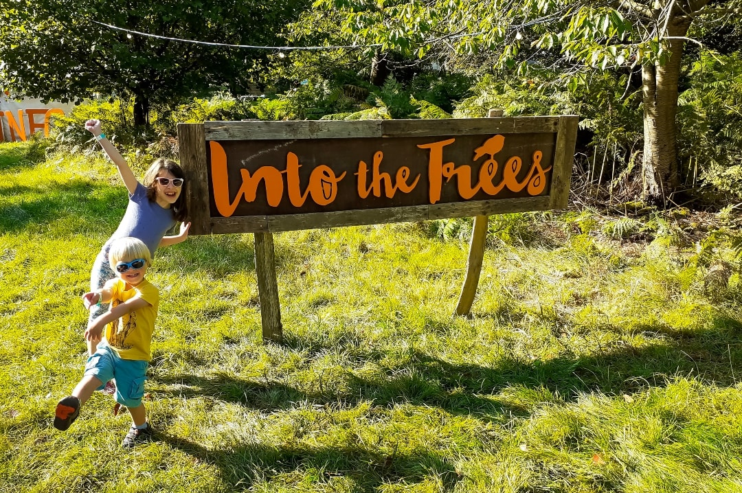 A photograph of a little girl and little boy standing in front of the Into The Trees sign at the Into The Trees festival 2019 - Into The Trees 2019 - An Idyllic Family Festival - Mrs H's favourite things