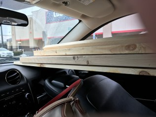 lumber protruding through vehicle passenger front seat