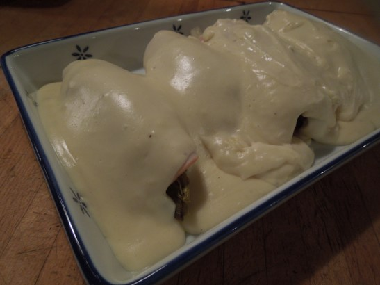 Image of ham-wrapped chicory with cheese sauce poured over