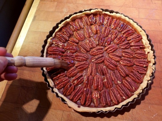 Image of honey glaze being brushed onto pecan topping