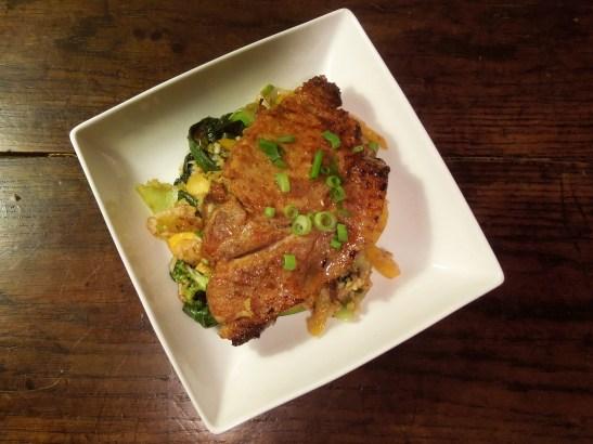 Image of pork steak served on stir-fried vegetables