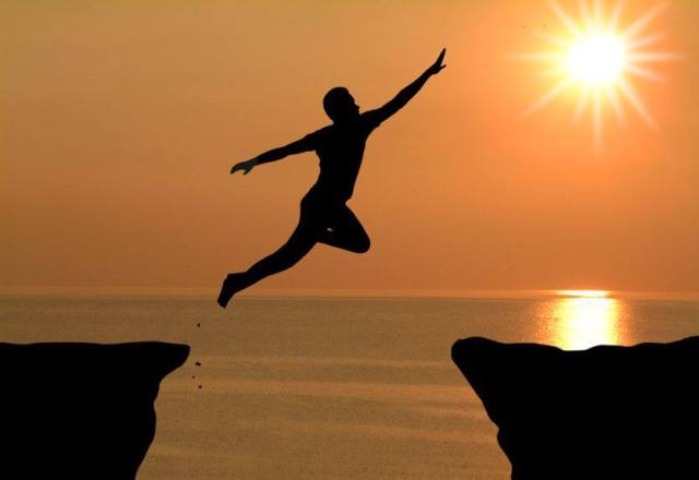 """Man jumping from one ledge to another. Taking a """"leap of faith"""""""