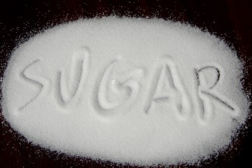 Pile of sugar spread out with the word sugar written in it. 12 quick questions to determine if you're a sugar addict