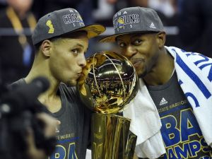 Stephen Curry and Andre Iguodala kissing the NBA trophy after 2015 championship