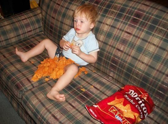Kid with bag of Doritos on couch