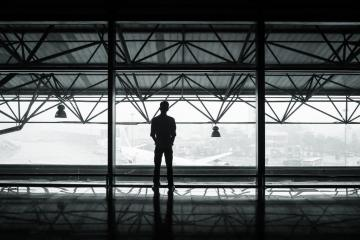 man looking outside a airport window at a airplane