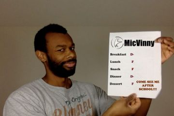 Michael V. Moore aka MicVinny holding a report card up with failing grades for breakfast, lunch, snack, dinner and dessert