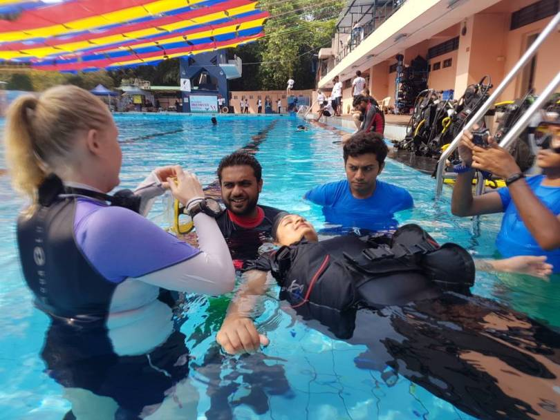 All set up for scuba diving with oxygen cylinder on my back, buoyancy control device (BCD) which looks like a life jacket but is more advanced. Here I am in the process of wearing my mask.