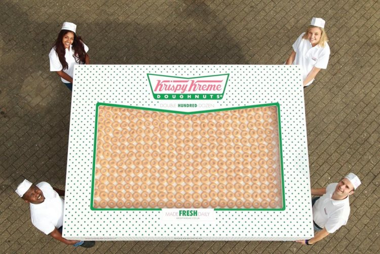 Four people stand around an enormous box of donuts.