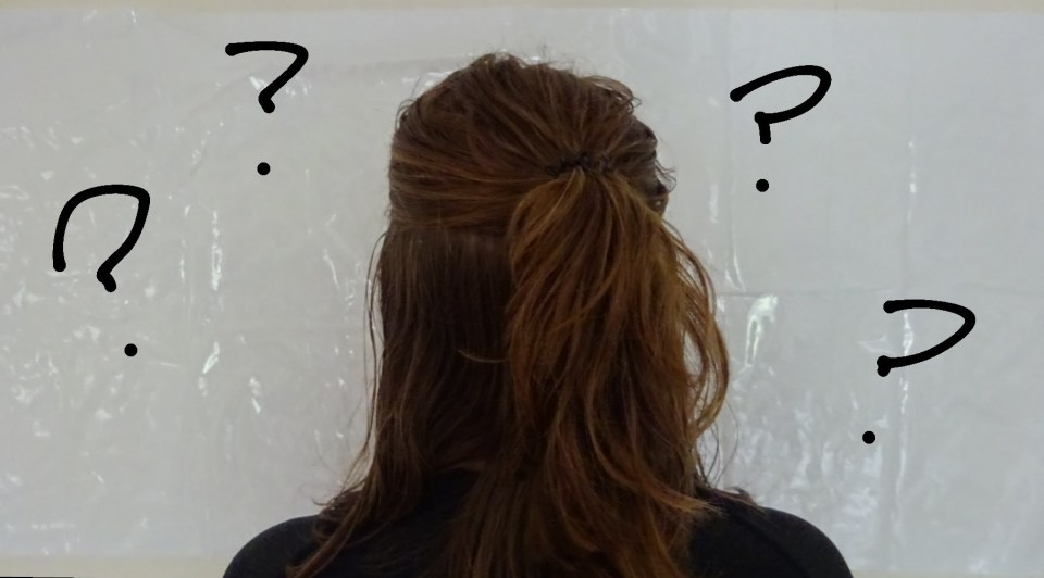 Me stood in front of a white background with question marks round my head symbolising all the factors that can impact intrinsic motivation