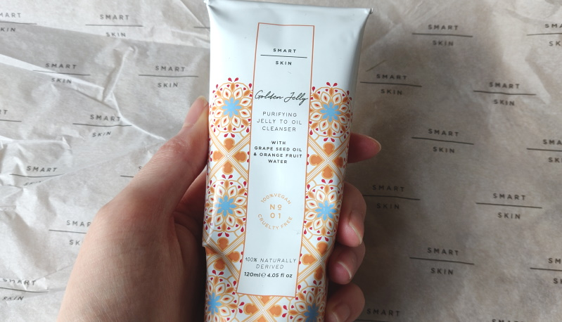 Smart Skin 'Golden Jelly Cleanser' being held with decorative background.
