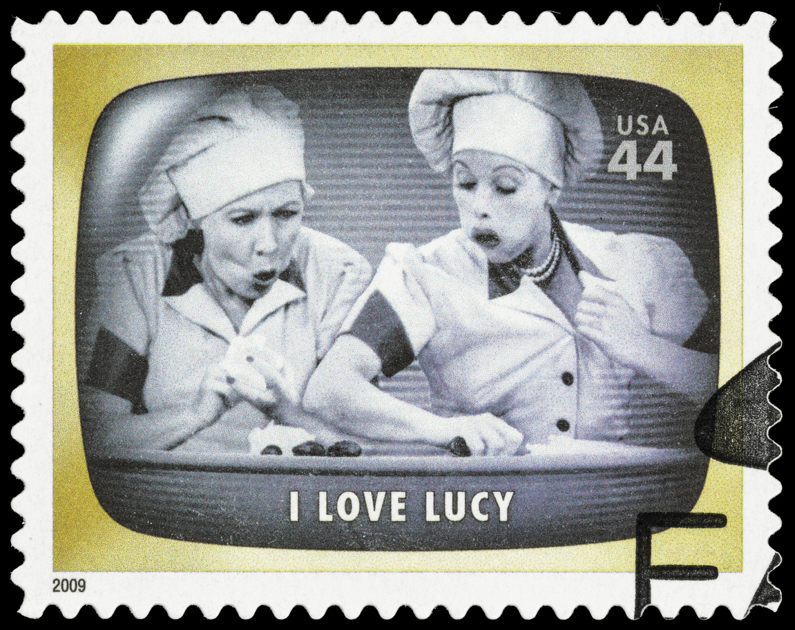 Postage stamp depicting Lucy and Ethel in chef hats eating chocolates off a conveyor belt.