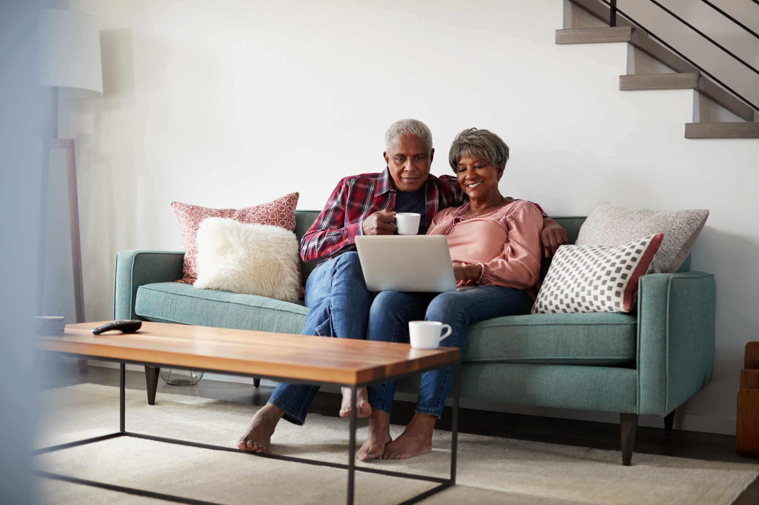 An elderly African American Couple using a laptop together.