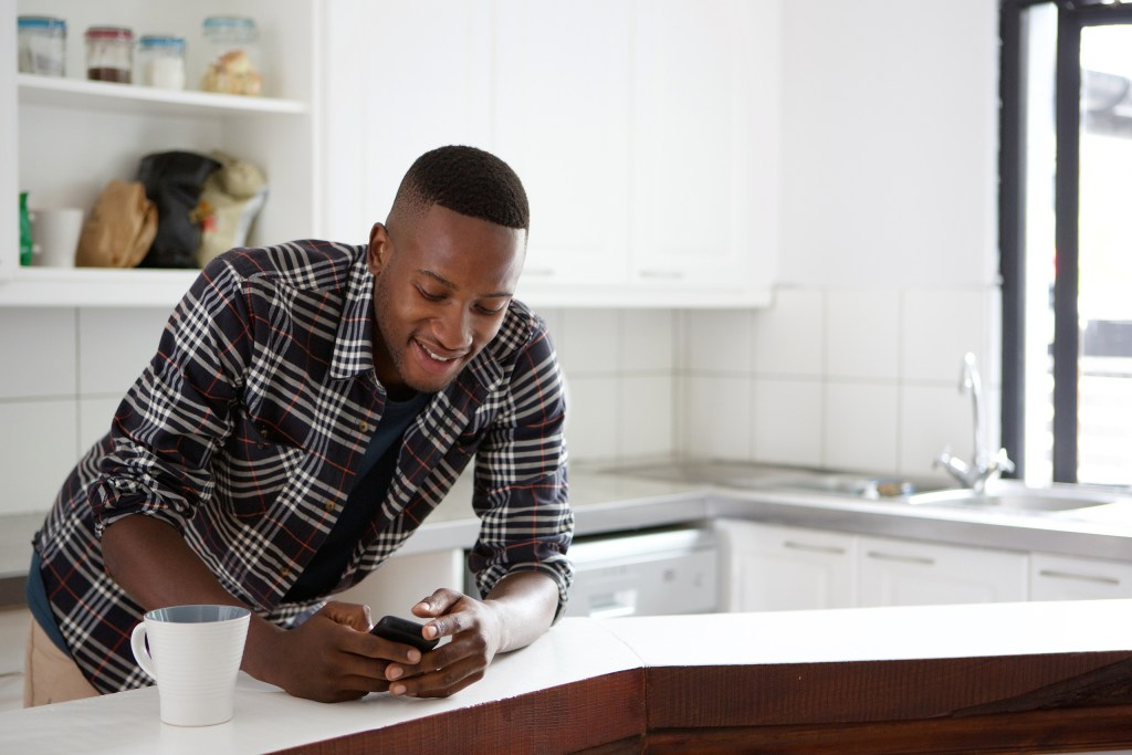 young african man standing at the kitchen counter on mobile phone