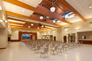 photo of interior large high-ceiling meeting hall with individual chairs set out in rows