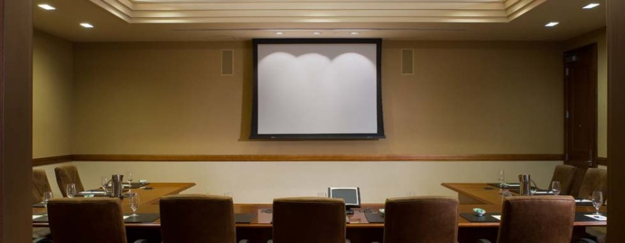 photo of long table beneath wall-mounted projection screen