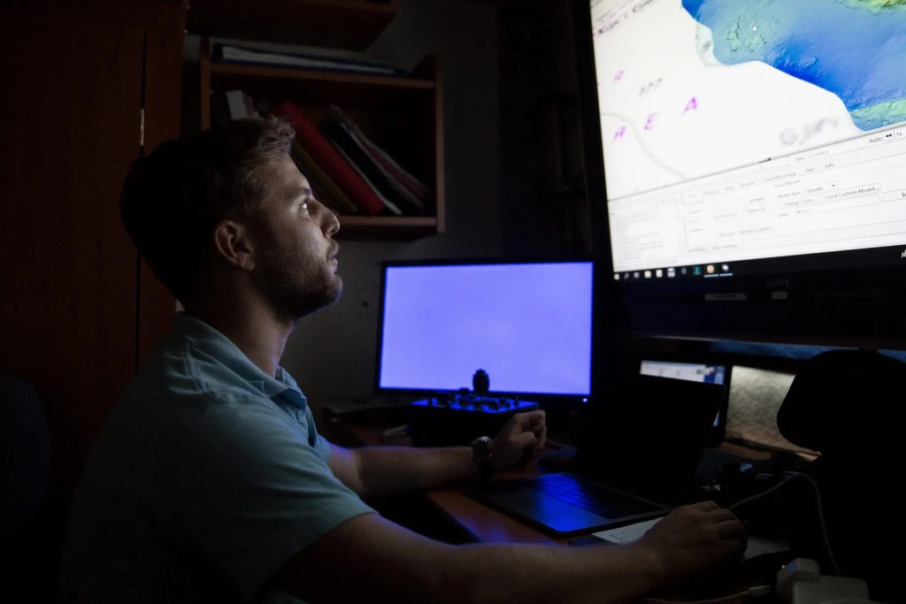 Mateusz Polakowski looking at a screen showing underwater site
