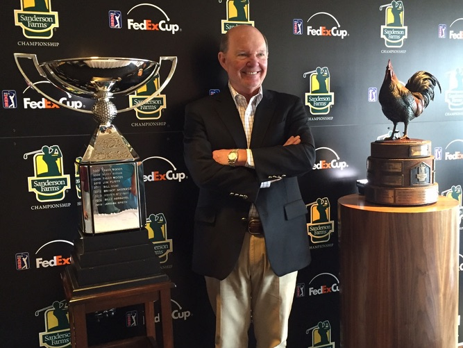 Joe Sanderson, with Fed Ex Cup Trophy on left and Sanderson Farms Championship trophy on right.