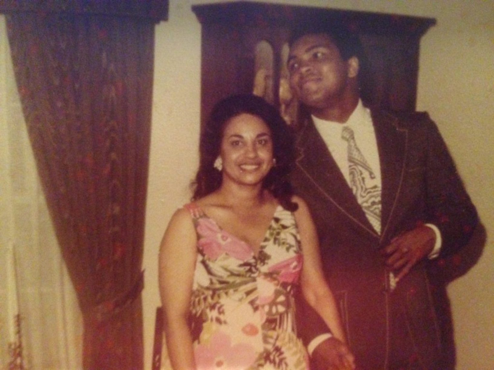 Muhammad Ali, with Betty Casem, peaks over to see himself in the mirror.