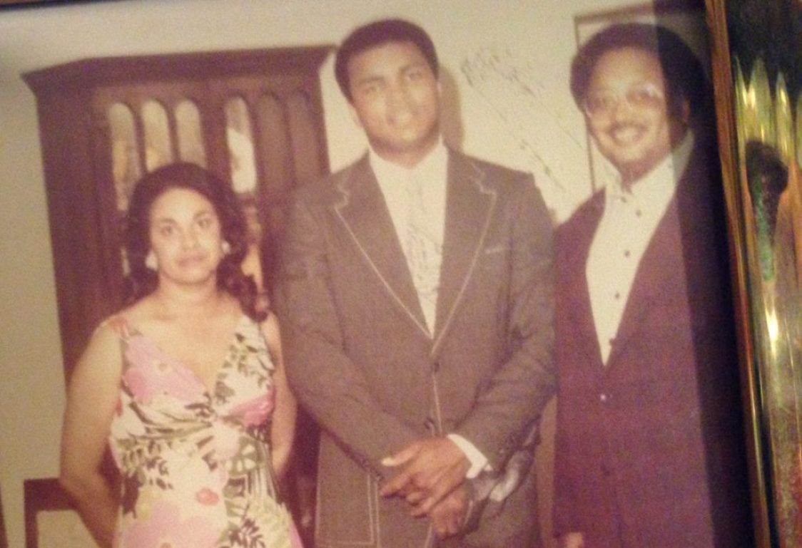Ali, flanked by Betty and Marino Casem in their Lorman living room in 1974.