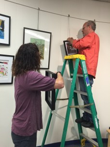 Committee member Victoria Plummer handing art to Nick Rizzo