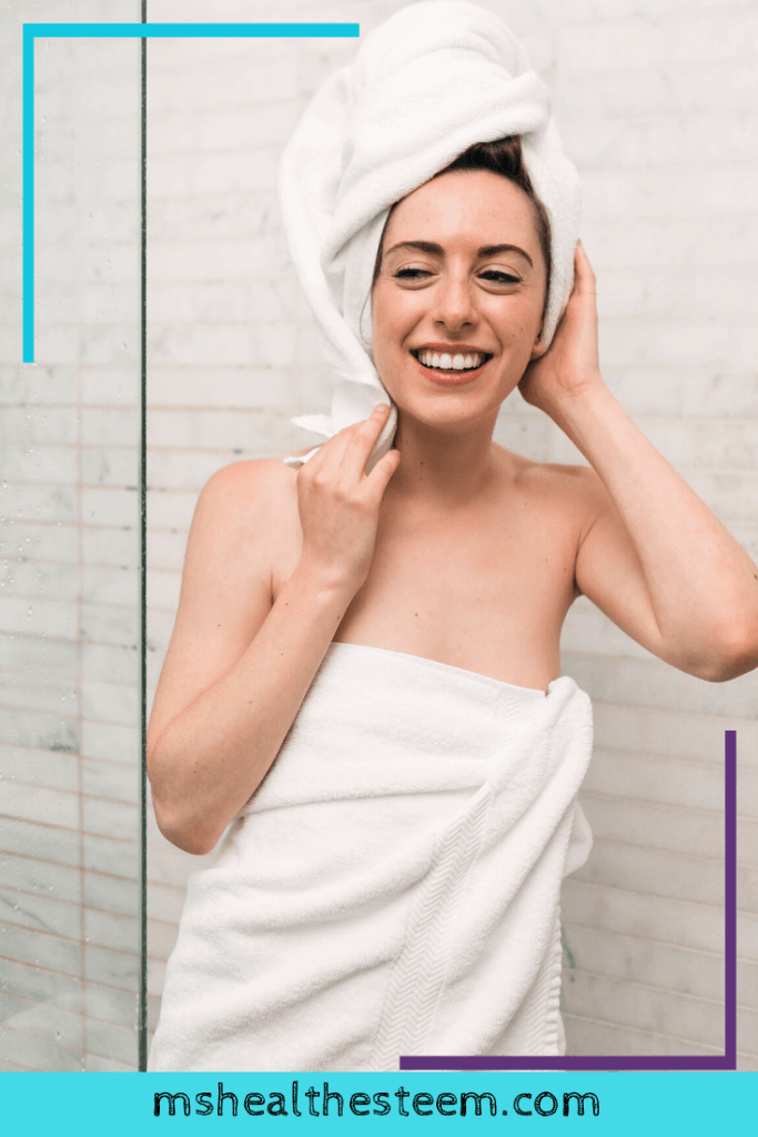 A woman inside her bathroom wrapped in a white towel