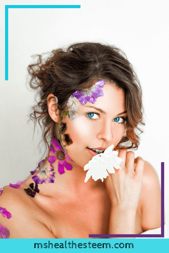 Brunette woman with bright blue eyes and flowers decoratively placed on the side of her face, neck and shoulder, holding a flower and looking at the camera