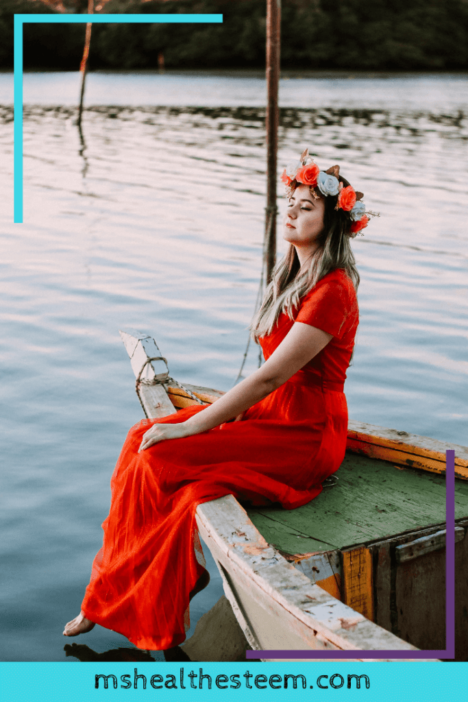 A woman in a gorgeous orange dress with an orange and white flower crown sits on the edge of a boat with her eyes closed in contemplation.