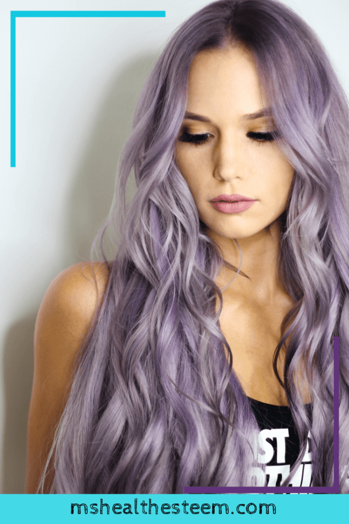 A protrait of a woman with long, purple hair. She looks down to the left, away from the camera.