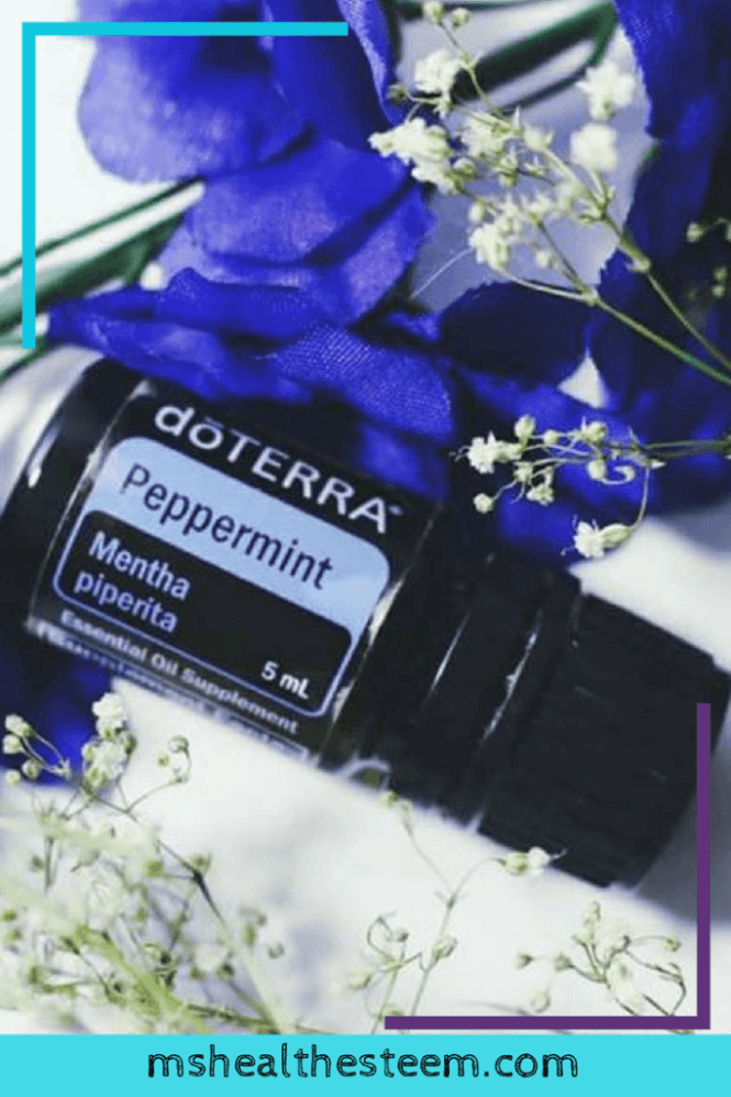 DoTERRA Peppermint essential oil surrounded by blue flowers and babies breath