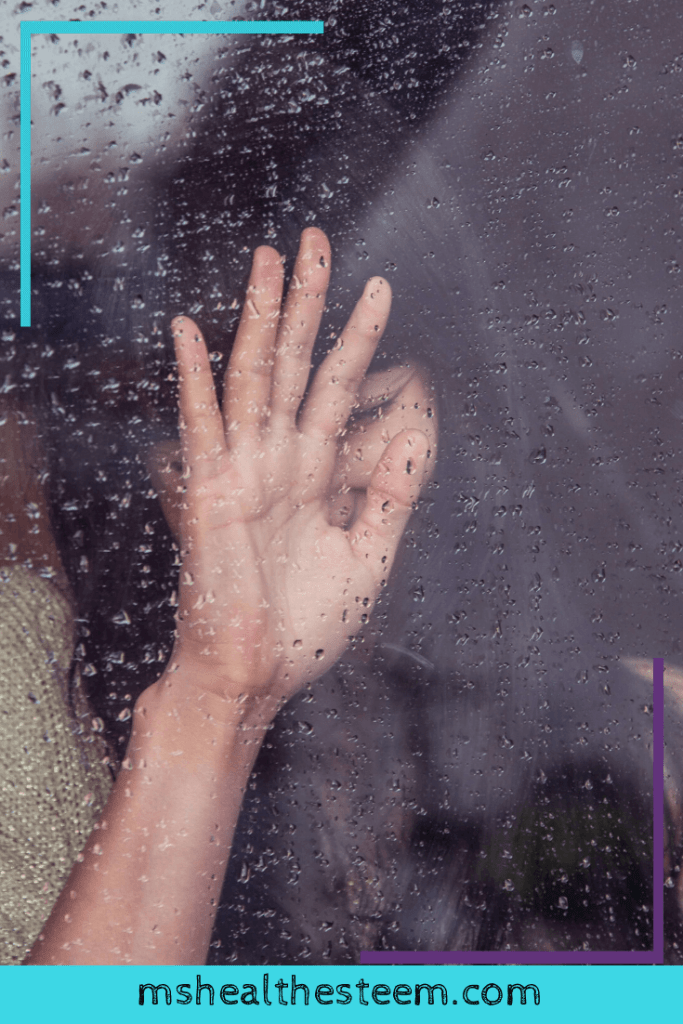 A woman places her hand on a window covered with rain droplets. Her hand blocks most of her face, but she appears to be smiling.