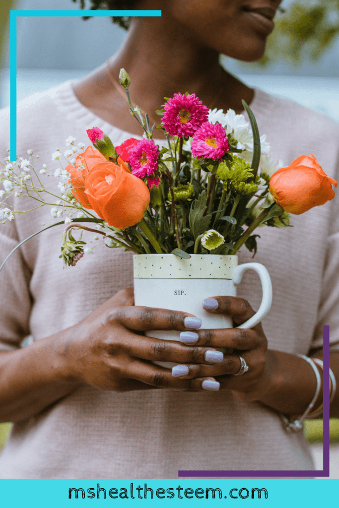 A woman holds a bouquet of flowers in a cup that says sip.