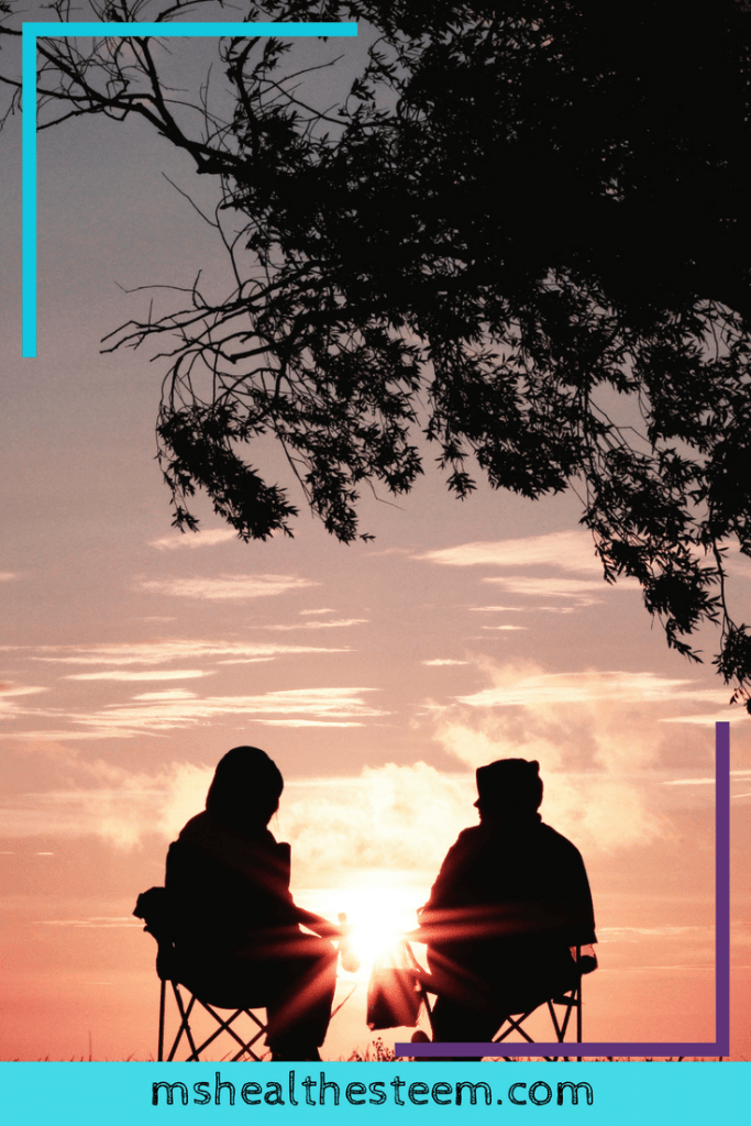 Two people sit in outside under a tree, watching the sun set. Time with loved ones can help to reduce stress