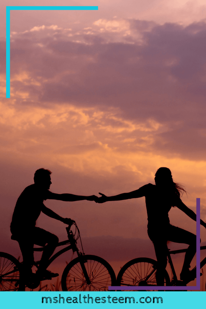 Two people bike in the dusk. One reaches back to grab the hand of the other. Exercise can greatly help to reduce stress.