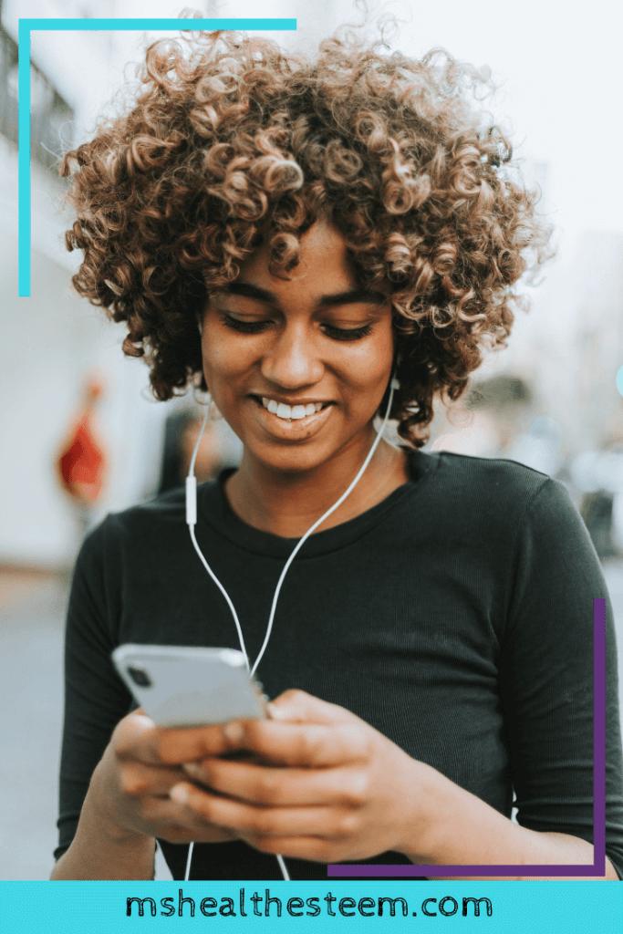 A woman wears headphones and looks down at the phone she's holding, smiling.