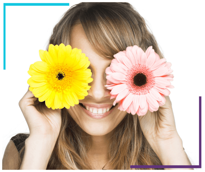 A woman holds a pink flower over her left eye and a yellow flower over her right eye. She's smiling.