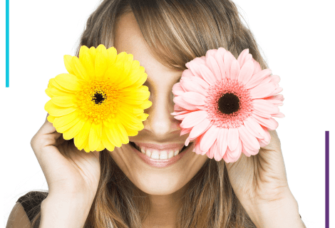 A woman holds a pink flower over her left eye and a yellow flower over her right eye. She