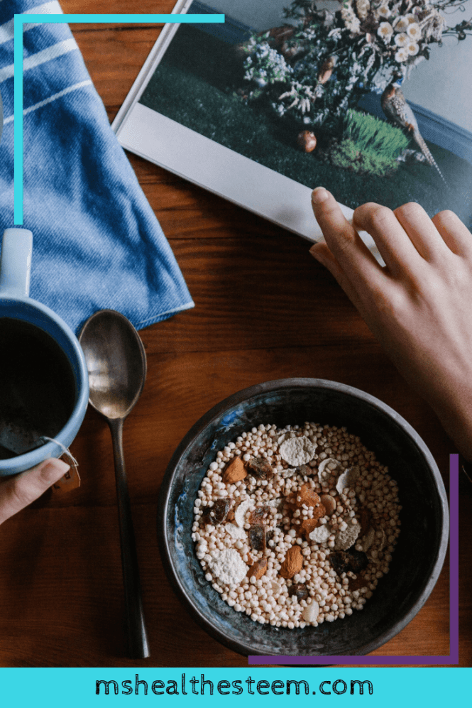 A flatlay of someone reading a book while eating their breakfast and enjoying a cup of coffee.
