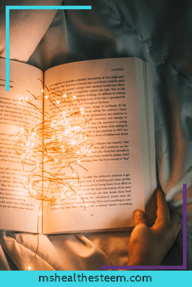 An open book lays resting on a bed in the dark, with some mini lights in between the pages providing enough light to read. One of the benefits of reading books before bed is that creating a night time routine helps you sleep.