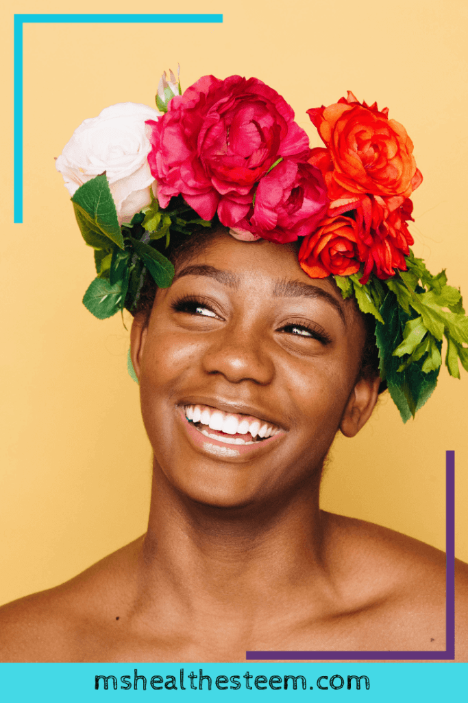 A portrait of a woman smiling as she wears a flower crown.