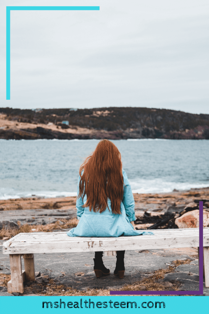 Someone with long red hair sits, back to the camera, enjoying the view of the water and scenery in a moment of self-care.