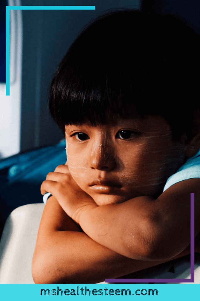 A little boy rests his head on his arms, looking sad