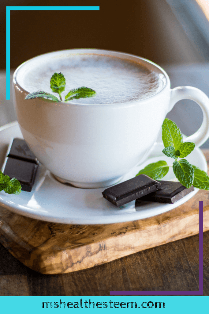 A cup of hot chocolate with mint leaves and chocolate pieces