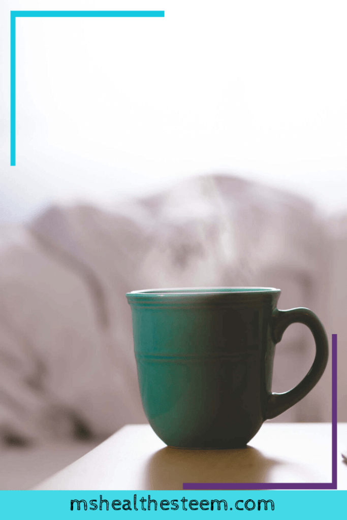 A steaming cup of tea sits on a bedside table
