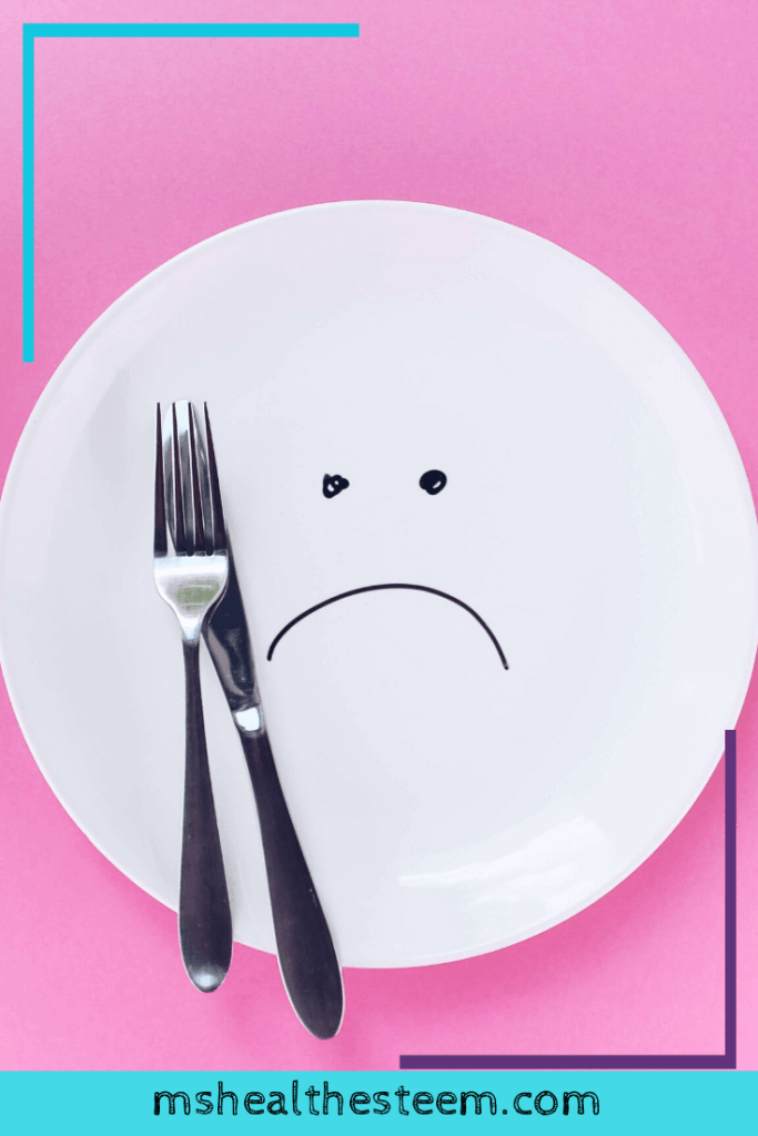 A plate with a sad face drawn on it. A fork and knife sit on top but there is not food. People often diet when trying to create lifestyle changes but they don't have to.