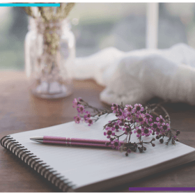 A journal sits open on a table, with purple flowers and a pen on top. In the background there's a vase with purple flowers in it and a white blanket that sits bundled on the edge of the table.