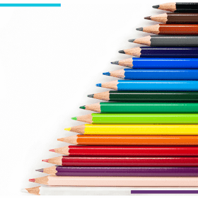 Many different colours of pencil crayons sit on a white backdrop, arranged diagonally